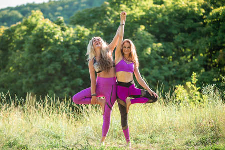 Two girls practice yoga in nature on a sunny day