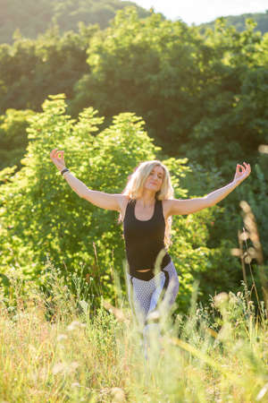 A slender girl does yoga in nature on a sunny day