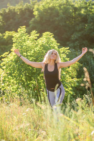 Slim woman practices yoga in nature on a sunny day