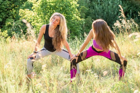 Woman yoga instructor shows a beginner how to do it right