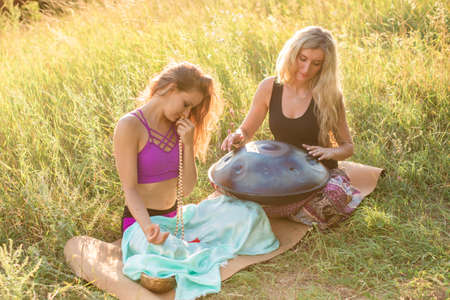 Young girls play and sing on the musical instrument Handpan. Practice meditation at sunset