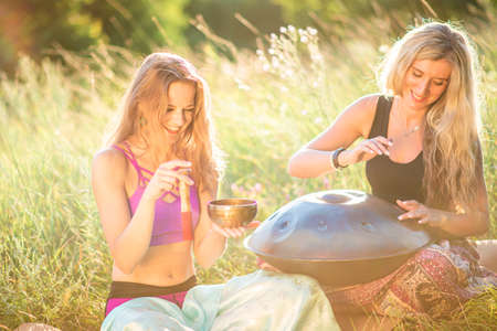 Young women play and sing on the musical instrument Handpan. Practice meditation at sunset