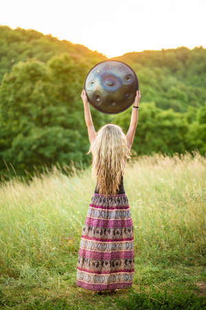 A young girl holds a Handpan musical instrument above her head. Sunset meditation 版權商用圖片