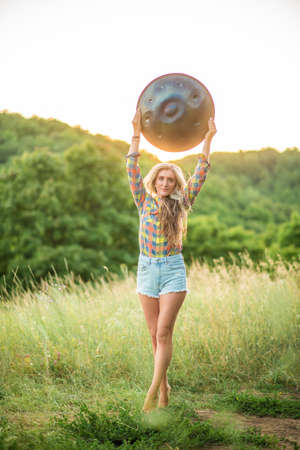 Young woman holds Handpan musical instrument above her head. Sunset meditation