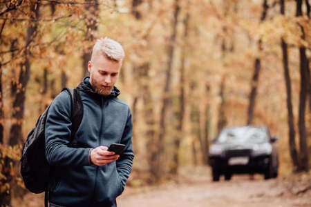 The man travels by car. The guy on the phone looks at where he is on the navigator. Hiker lost in the autumn forest concept.
