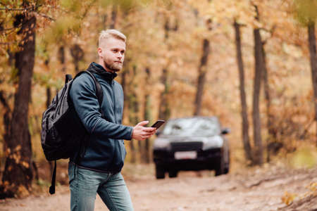 The tourist travels by car. The man in the phone looks where he is on the navigator. The guy got lost in the autumn forest concept.