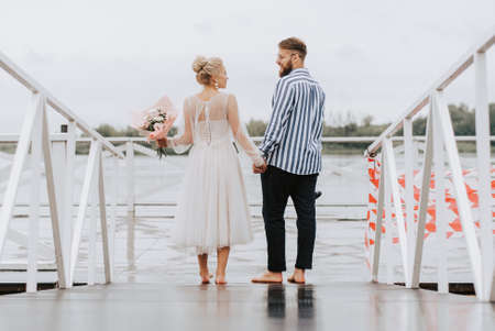 The just married on the wharf. The bride and groom walk barefoot along the pier.