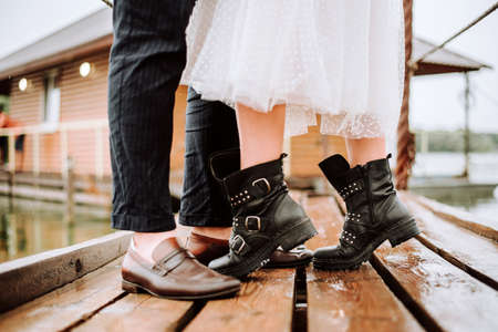 Legs of the just married on the background of the wharf. The bride and groom stand and pose in boots on the pier.