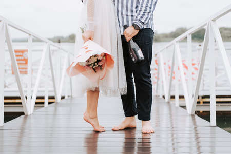 Foots of the just married on the wharf. Legs of the bride and groom barefoot on the pier.