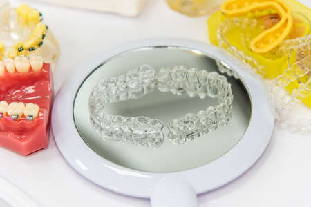 Invisible aligner teeth retainers lie on the mirror in orthodontic office Stok Fotoğraf