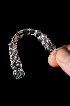The guy holds in his hand transparent aligners plastic braces retainers for straightening teeth on a black background