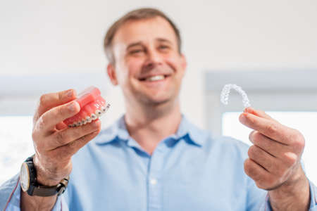 Dental care.Smiling orthodontist doctor holding aligners and braces in hand shows the difference between them