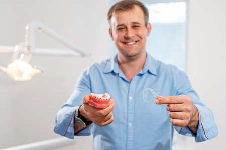 Dental care.Smiling dentist doctor holding aligners and braces in hand shows the difference between them Stok Fotoğraf