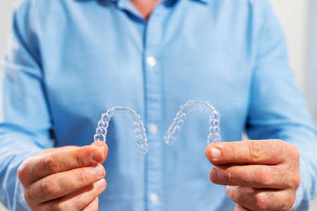 The dentist doctor holds transparent aligners in his hands