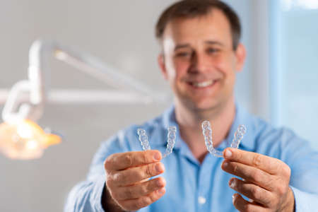 Smiling orthodontist doctor holds transparent aligners in his hands Stok Fotoğraf