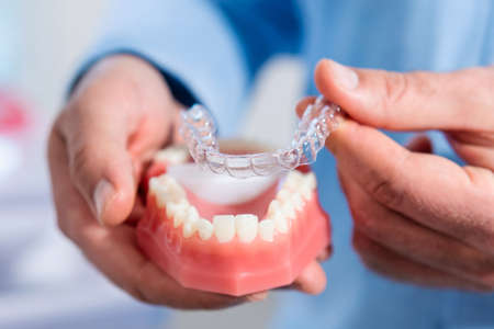 Close-up. The doctor puts transparent aligners on the teeth of the artificial jaw