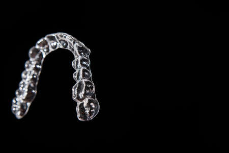 Invisible aligner teeth retainers on a black background