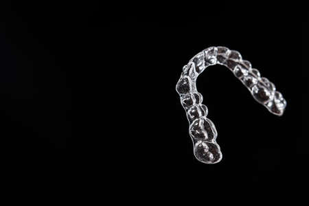 Invisible dental teeth brackets tooth aligners on black background. Plastic braces dentistry retainers to straighten teeth.
