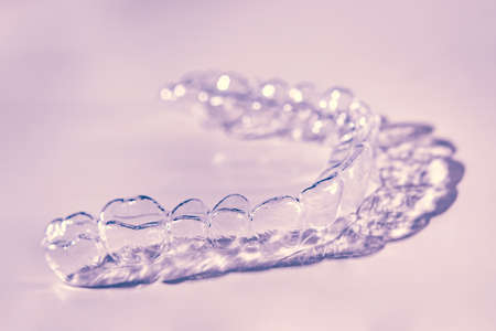 Invisible dental teeth brackets tooth aligners on pink background. Plastic braces dentistry retainers to straighten teeth.