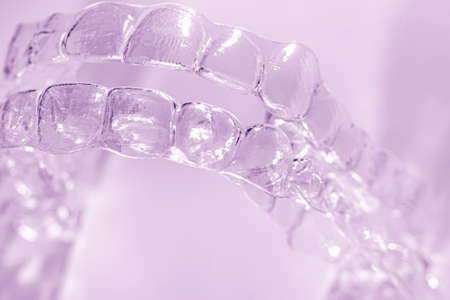 Invisible aligner teeth retainers on a purple background Stok Fotoğraf