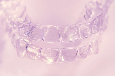 Invisible aligner teeth retainers on a pink background