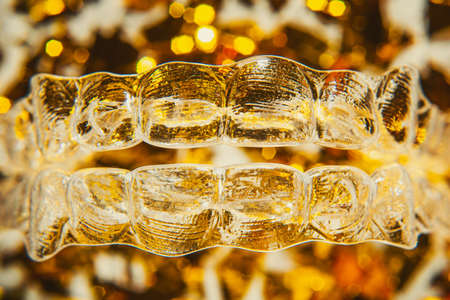 Invisible aligner teeth retainers on a gold background