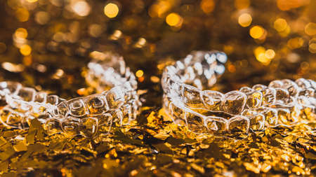 Invisible dental teeth brackets tooth aligners on gold background. Plastic braces dentistry retainers to straighten teeth.