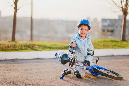 A small child in a helmet and protection fell from a bicycle onto the asphalt and was not injured