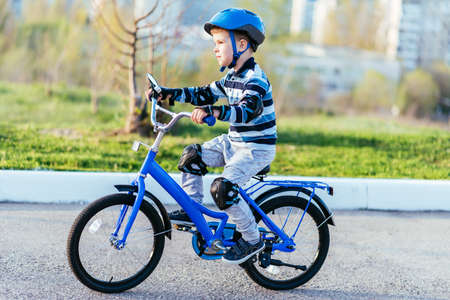 A child in a helmet and protection rides a bicycle on the road