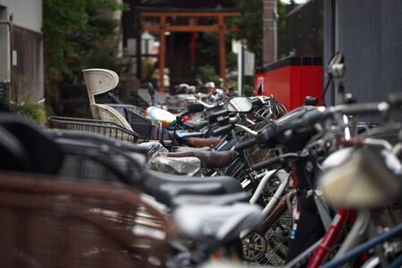 Bicycles in Kyoto, Japan, where riding a bike is a major form of transportation. There is a row of bikes, leading to a Shinto Gate, where residents park as they shop in the local area.