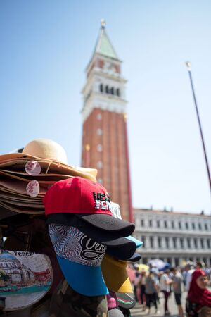 Souvenir hats being sold in Piazza San Marco in Venice, Italy with the Campanile di San Marco in the background.