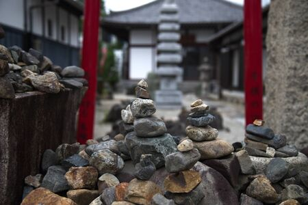 Stacked rocks and pebbles in front of a Shinto gate and shrine in Kyoto, Japan.