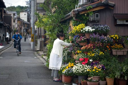 KYOTO, JAPAN - APRIL 24, 2018 A woman in Kyoto, Japan tending to her plants and flowers.