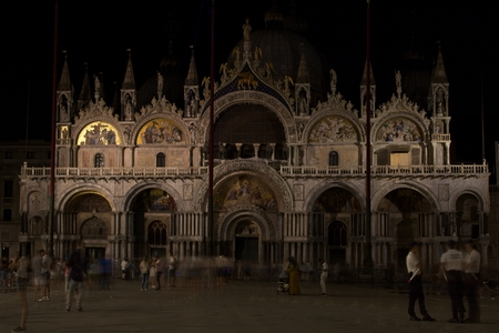 VENICE, ITALY - JUNE 16, 2019 - An evening photo of Saint Marks Basilica in Venice, Italy. Venetians, policemen, and tourists are walking around San Marco Square.
