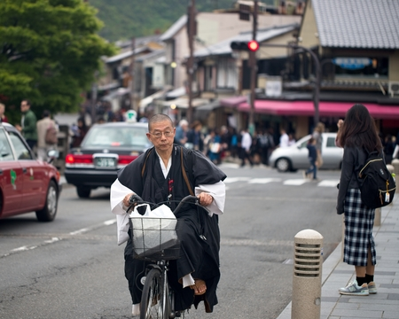 KYOTO, JAPAN - APRIL 24, 2018 - A monk riding a bicycle in Kyoto, Japan. In the background is a Japanese schoolgirl and many tourists visiting the Arashiyama area. Редакционное