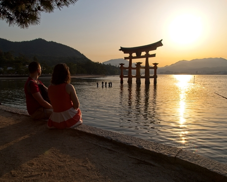 A couple looks upon the Great Torii, a very large Shinto gate, as the sun sets on Miyajima, Japan.