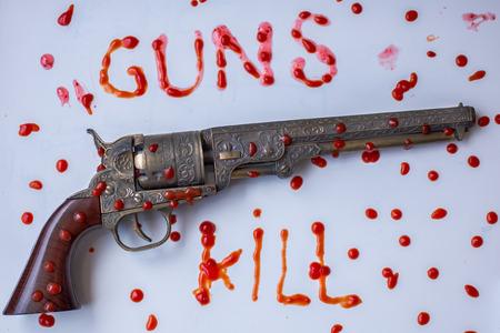 splats: Gun control concept, Guns Kill, showing a gun and splats of blood.
