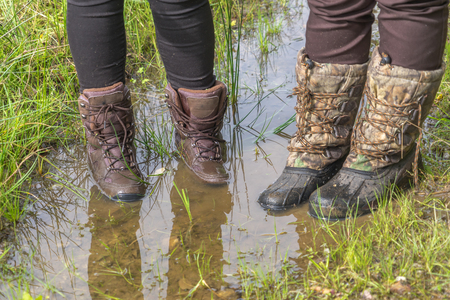 walking boots: Hikers standing in muddy walking boots in a puddle. Stock Photo