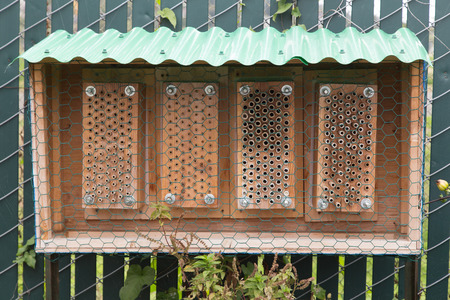 man made: Man made bee hive hanging on a fence