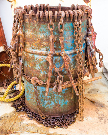 Rusty chainbinders in a barrel Stock Photo