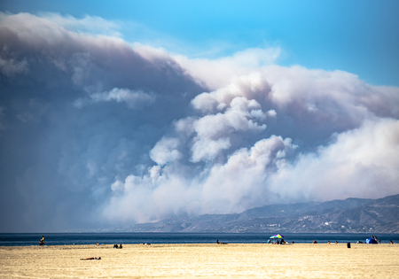 Smoke covers blue sky as wildfire erupts in coastal California mountains. Photo taken across ocean from beach Stock Photo