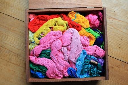 Cheveaux colorés de fil à broder dans une boîte en bois. Banque d'images - 20685419
