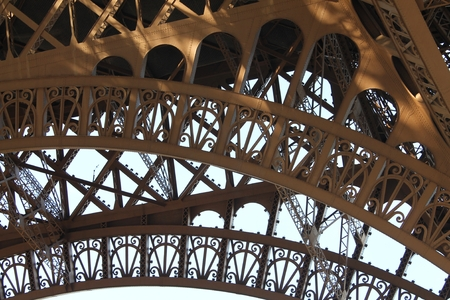 ironwork: Detail of the ornate ironwork of the arches of the Eiffel Tower in Paris, France.