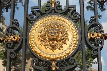 A golden lion medallion set in an ornate wrought iron gate in Paris, France.