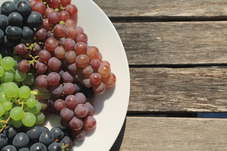 concord grape: A white plate full of freshly picked bunches of blue, green and purple grapes on a weathered wooden table Stock Photo