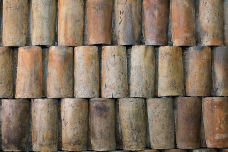 Weathered handmade clay roof tiles set in mortar to create a patterned wall in Chordeleg, Ecuador, Central America