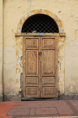stucco facade: An ancient door with colorful faux painted wood grain set in a crumbling stucco facade on the street in Cuenca, Ecuador Stock Photo