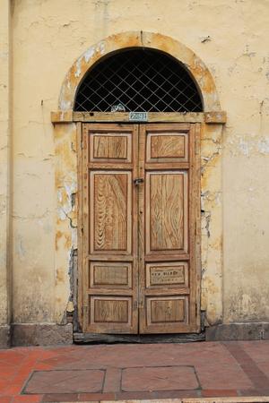 stucco facade: Un'antica porta con colorato finto dipinte venature del legno situato in una facciata in stucco fatiscente sulla strada a Cuenca, Ecuador