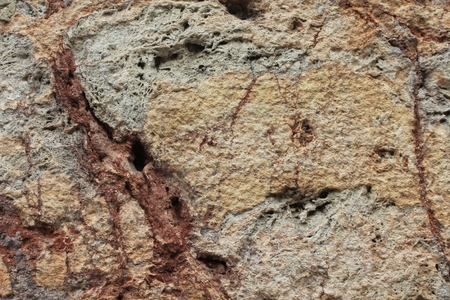 tooled: Rough textured stone building block with veins of ochre and tan running through. Horizontal weathered background. Stock Photo
