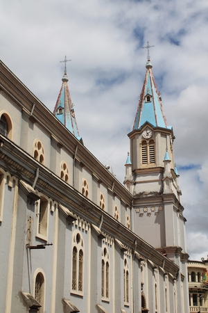 steeples: Looking up at the blue-roofed twin steeples of Iglesia de San Alfonso cathedral in Cuenca, Ecuador, one of more than 50 churches in the popular South American city. Stock Photo